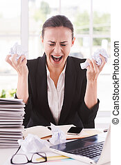 Sick and tired. Furious young woman in formalwear holding papers in hands and shouting while sitting at her working place
