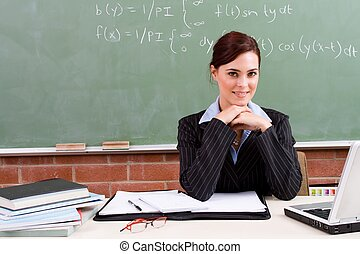teacher in classroom posing at desk