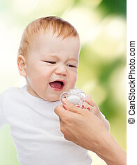 crying baby with dummy - child and toddle concept - crying...