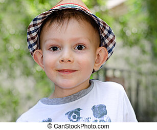 Cute little boy with a wide-eyed expression wearing a...