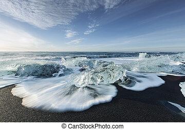 Ice melting on the beach - Melting ice on beach near...