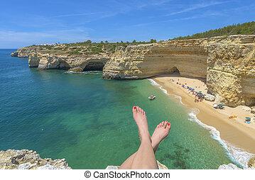 Tourist enjoying a beach view from a cliff