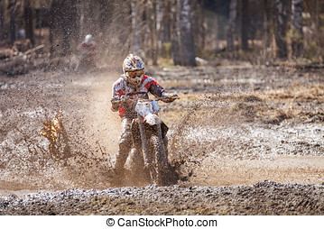Motocross driver in mud