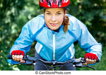Happy Young woman leaned over the handlebars of her bike