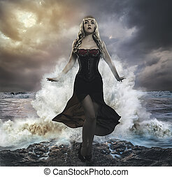 the forces of nature, blonde woman on the rocks with the sea...
