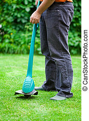 man mowing lawn with grass trimmer