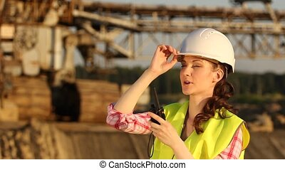 The girl in a helmet looks at the working excavator
