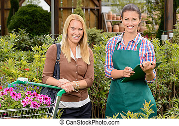 Customer and worker in garden center smiling