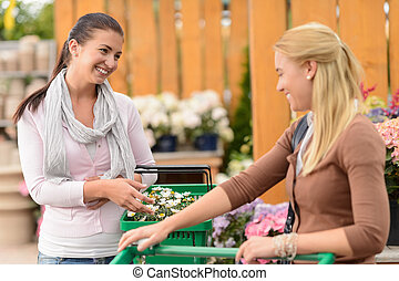 Two smiling woman shopping plants garden center - Two...