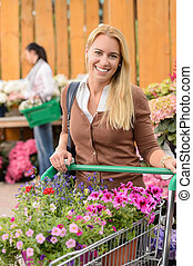Woman buying flowers shopping cart garden center - Smiling...
