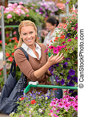 Woman shopping for colorful flowers garden center - Smiling...