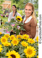 Smiling customer woman shopping for potted sunflower in...