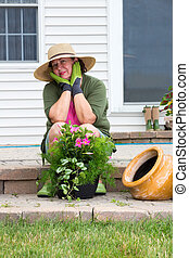 Stylish Grandma in gumboots and sunhat seated on the brick...