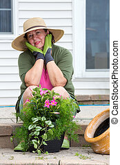 Attractive senior woman potting up plants - Attractive...