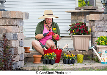 Senior lady potting up plants in flowerpots - Senior lady...