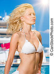 Young woman posing is front of super yacht