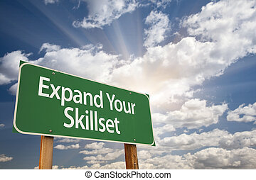 Expand Your Skillset Green Road Sign with Dramatic Clouds...