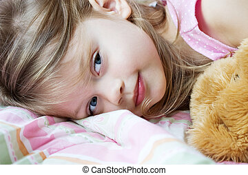 Toddler lying in bed with her teddy bear
