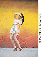 Young woman in pink sexy dress against color wall