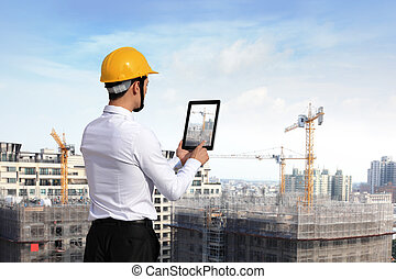architect - Rear view of architect looking tablet pc and...