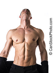 Handsome muscular young man taking off shirt, isolated on...