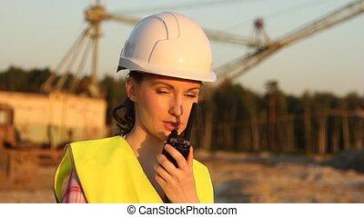 Pretty woman in helmet discusses something by walkie talkie...