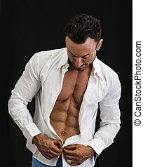 Male bodybuilder opening his shirt revealing muscular torso,...