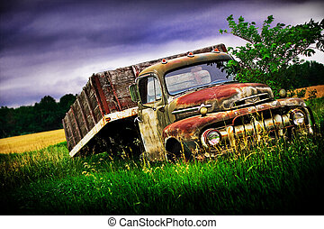 Ford Truck - Old Ford truck in a green pasture with a dark...