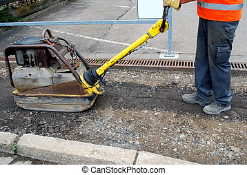 road construction worker with road roller or compactor