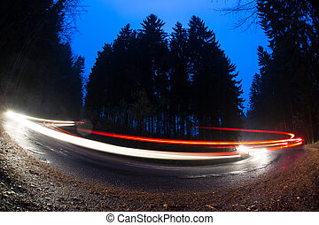 Cars going fast through a curve on a forest road at dusk