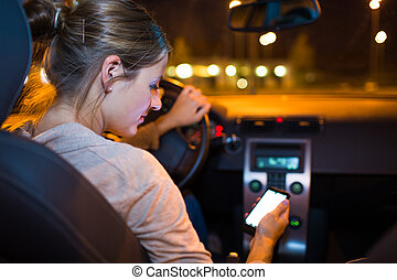 Pretty young woman using her smart phone while driving her...