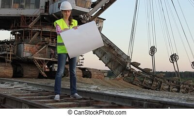 Woman with drawing on huge excavator on background