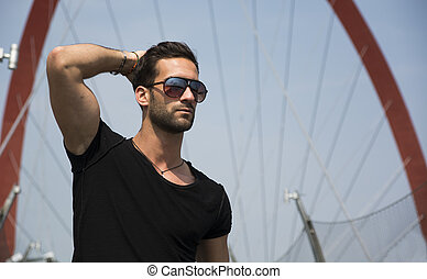 Young man outdoors in front of Olympic Arch in Turin, Italy...