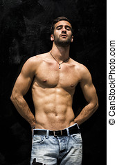 Handsome bearded shirtless young man standing against black...