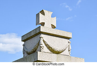 war memorial with stone cross and wreath