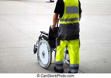 wheel chair airport - airport worker providing a wheelchair...