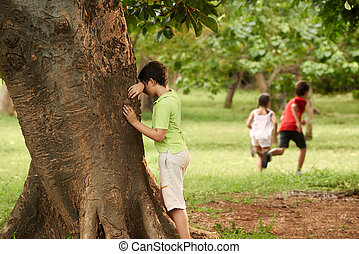 male and female children playing hide and seek - young boys...