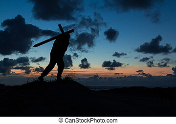 Cross Carrier - Man carrying a cross at dusk