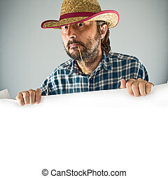Farmer with cowboy straw hat holding blank poster as copy...