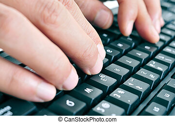 typing on a computer keyboard - closeup of the hands of a...