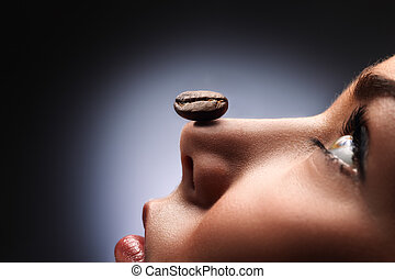 Smell and relax - A black roasted coffee bean on the nose of...