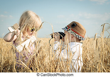 Two little children playing in a wheat field - Two trendy...
