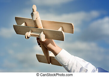 Hand of a child playing with a wooden airplane toy