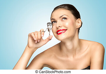 Curling lashes - A beautiful fashion girl holding an eyelash...