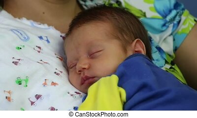 Newborn sleeping in mother arms