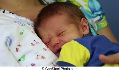 newborn baby boy yawning in the arm