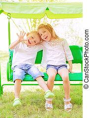 Brother and sister on the swing - Cute little brother and...