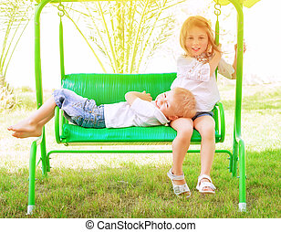 Spending time on swing - Two adorable child spending leisure...
