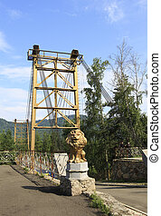 Golden lion sculpture and Suspension Bridge on the Katun River.