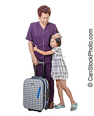 Senior woman hugging crying girl with suitcase.